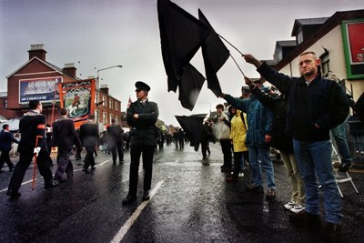 Catholics stand in silence holding black flags as Orangemen march past down the Lower Ormeau Road